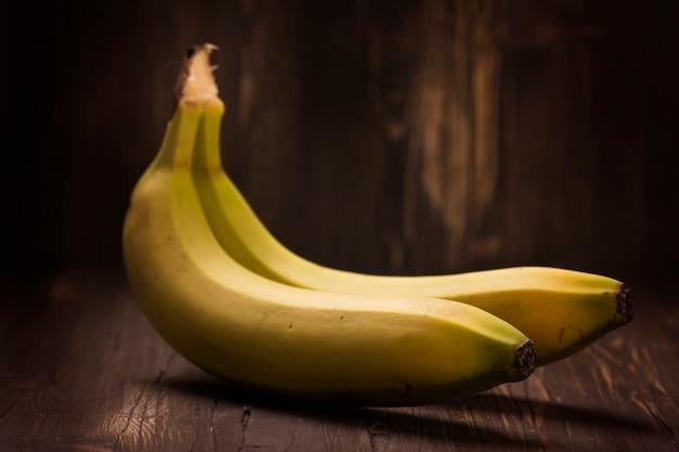 Cacho de bananas maduras sobre fundo de madeira rústico