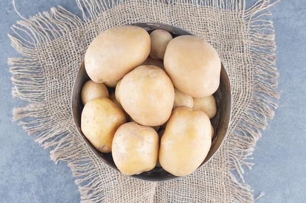 Cacho de batatas em caneca de metal com serapilheira.