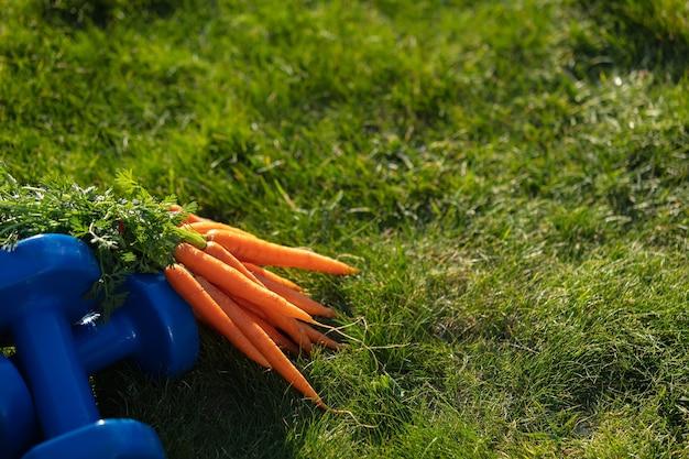 Cacho de cenouras e halteres na grama verde do jardim