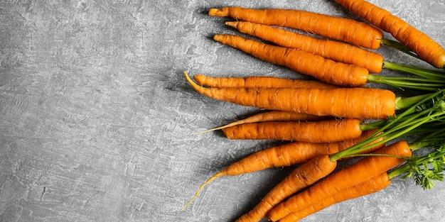 Cacho de cenouras frescas e orgânicas em vista aérea de uma cozinha cinza