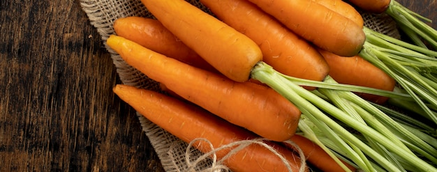 Cacho de cenouras frescas na mesa de madeira
