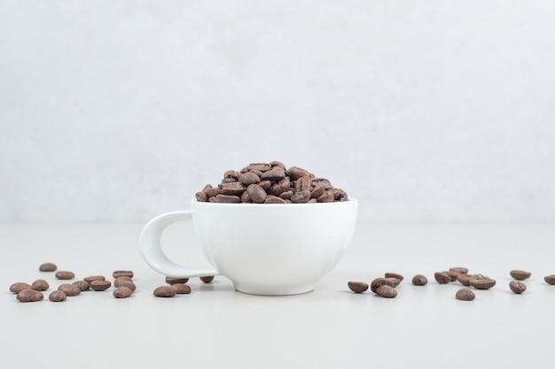 Cacho de grãos de café em caneca branca