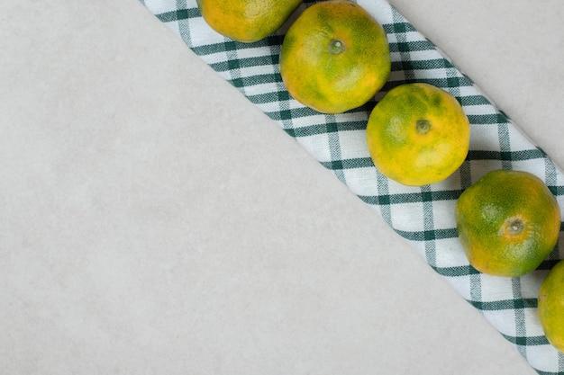 Cacho de tangerinas verdes em toalha de mesa listrada
