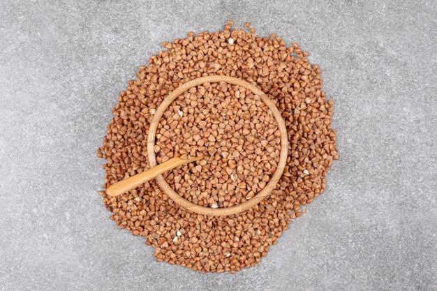 Cacho de trigo sarraceno cru em tigela de madeira