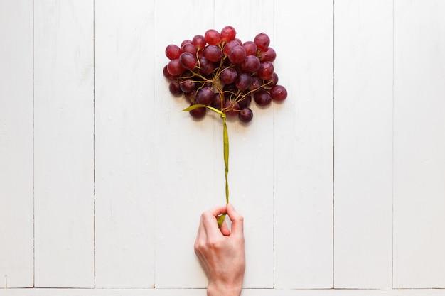 Cacho de uvas, amarrado com uma fita na mão de uma mulher