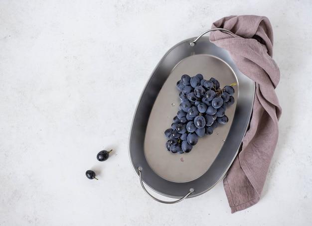Cacho de uvas azuis em um prato sobre um fundo claro