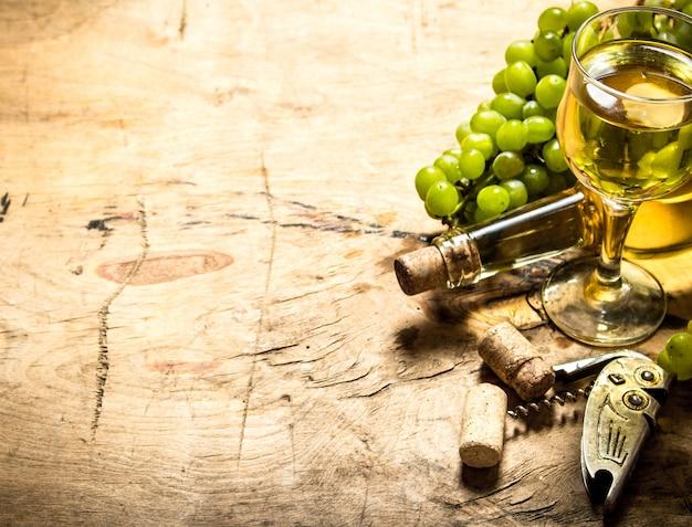 Cacho de uvas brancas com vinho, saca-rolhas e rolhas. em fundo de madeira.