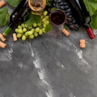Cacho de uvas com garrafa de vinho no fundo de mármore