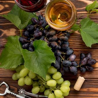 Cacho de uvas com saca-rolhas em fundo de madeira