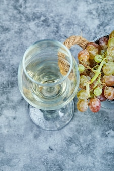 Cacho de uvas e uma taça de vinho no azul.
