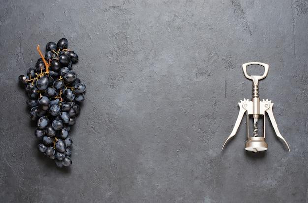 Cacho de uvas pretas e um saca-rolhas.