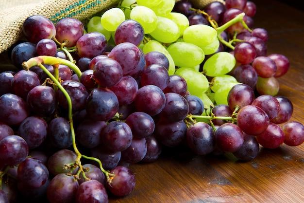Cacho de uvas pretas e verdes sobre fundo de madeira