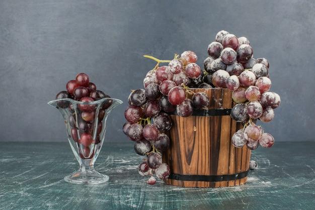 Cacho de uvas pretas em vidro e balde de madeira.