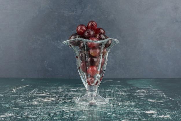 Cacho de uvas pretas em vidro na mesa de mármore.