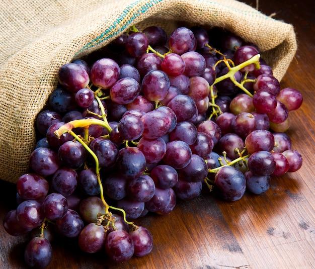 Cacho de uvas pretas na madeira