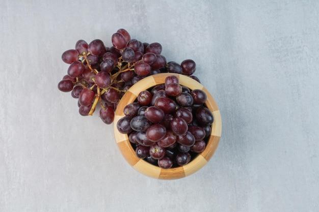 Cacho de uvas roxas no balde e na mesa. foto de alta qualidade
