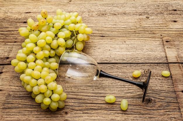 Cacho de uvas sem sementes verdes doces e copo de vinho