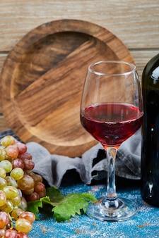 Cacho de uvas, um copo de wone tinto e uma garrafa de wone em azul e de madeira.