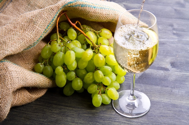 Cacho de uvas verdes e vinho na madeira