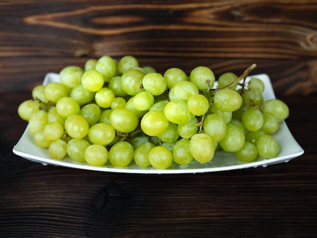 Cacho de uvas verdes em madeira