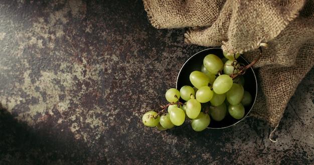 Cacho de uvas verdes em um fundo escuro.
