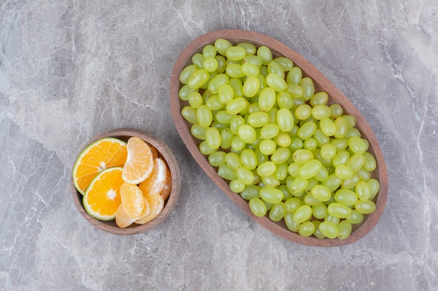 Cacho de uvas verdes em uma tigela de madeira e frutas cítricas.
