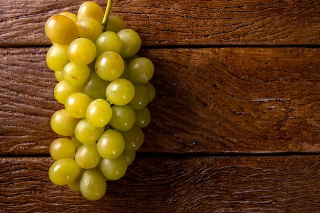Cacho de uvas verdes, frutos de outono, um símbolo de abundância em fundo de madeira rústico.