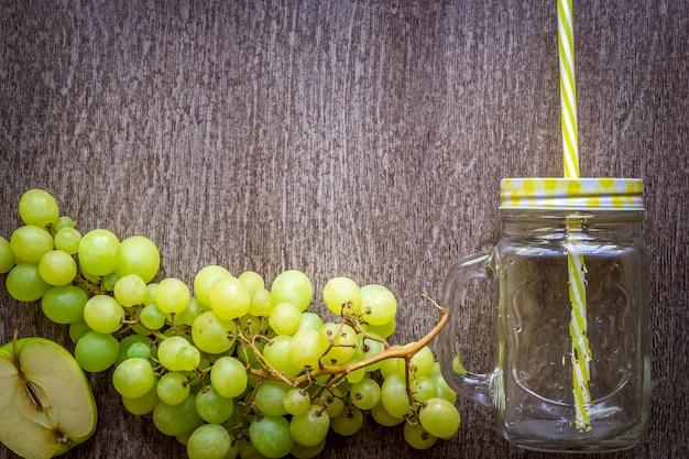 Cacho de uvas verdes frutos do outono em fundo de madeira rústica
