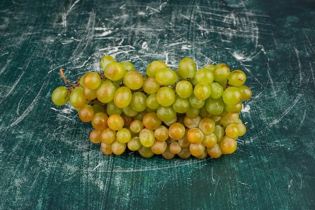 Cacho de uvas verdes na mesa de mármore