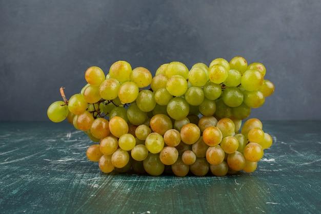 Cacho de uvas verdes na mesa de mármore.