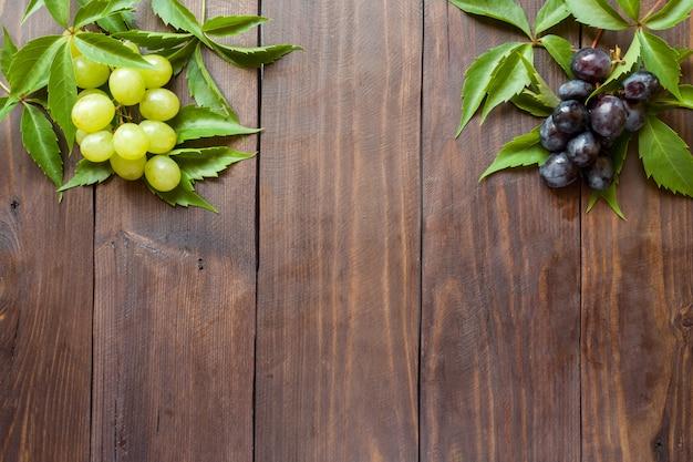 Cacho de uvas vermelhas e brancas sobre fundo de mesa de madeira