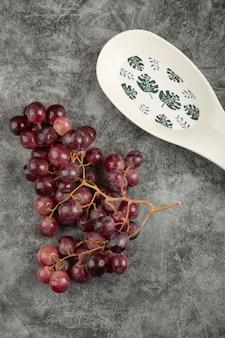 Cacho de uvas vermelhas e prato branco vazio na superfície de mármore.