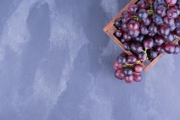 Cacho de uvas vermelhas em uma travessa rústica.