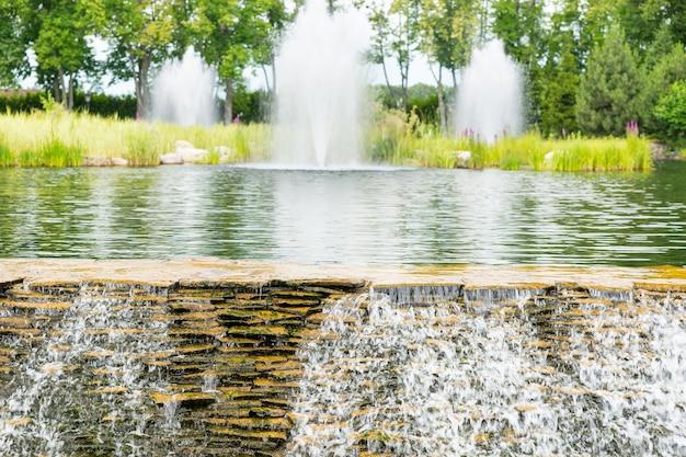 Cachoeira artificial em um parque com lago, fonte e diferentes árvores ao fundo