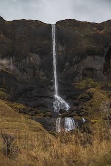 Cachoeira cercada por pedras e grama seca sob um céu nublado