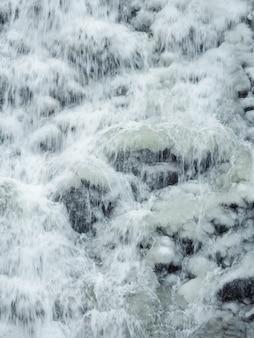 Cachoeira da montanha congelada. cachoeira com gelo. fundo de inverno. visão vertical.