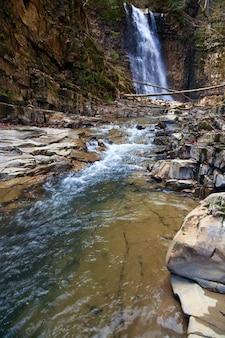 Cachoeira de alta montanha na floresta selvagem escura dos cárpatos (manjava, região de ivano-frankivsk, ucrânia).