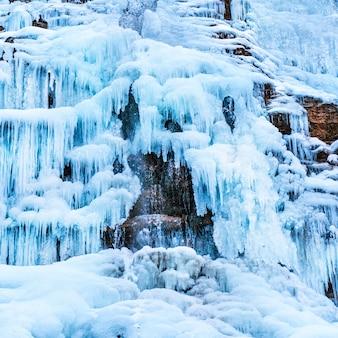 Cachoeira de gelo congelada de pingentes de gelo azuis na rocha