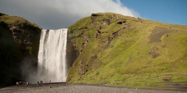 Cachoeira de skagafoss sobre o penhasco gramado com turistas