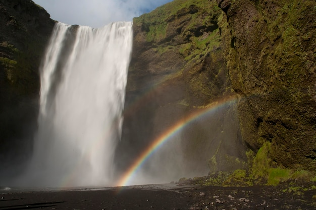 Cachoeira em cascata sobre um penhasco verde da rocha, com um arco-íris duplo vindo da névoa do lago