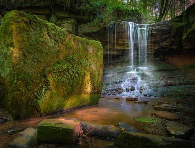 Cachoeira fluindo pela floresta durante o dia