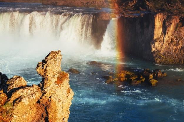 Cachoeira godafoss ao pôr do sol. arco-íris fantástico. islândia, europa