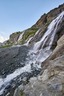 Cachoeira nas montanhas do cáucaso, derretendo cume da geleira arkhyz, sofia cachoeiras. belas montanhas altas da rússia, o rio de água gelada pura. verão nas montanhas, caminhada
