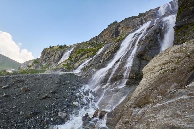 Cachoeira nas montanhas do cáucaso, derretendo o cume da geleira arkhyz, sofia cachoeiras. belas montanhas altas da rússia, o rio de água gelada pura. verão nas montanhas, caminhada