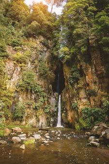 Cachoeira natural fluindo entre duas rochas.