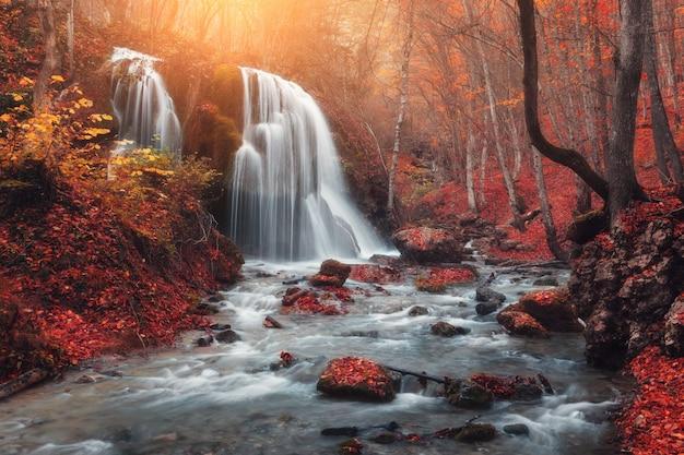Cachoeira no rio da montanha na floresta de outono ao pôr do sol