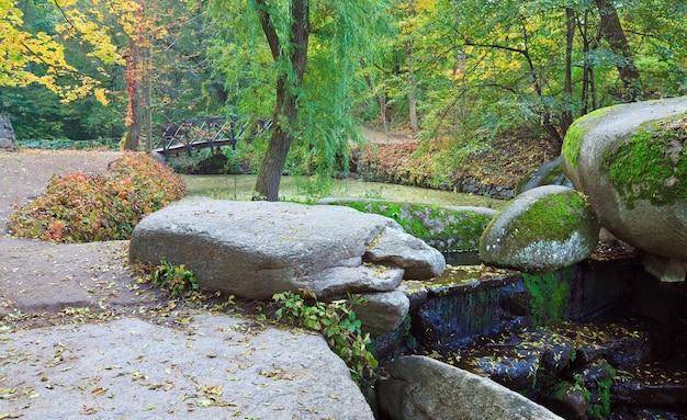 Cachoeira pequena, lago e ponte no parque outono