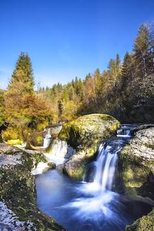 Cachoeira pequena na montanha com gelo em ain, frança