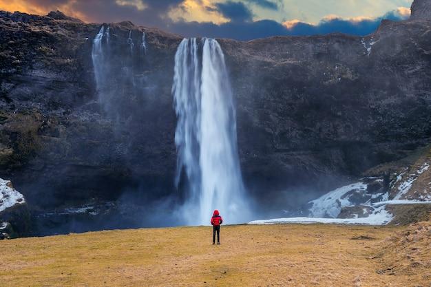 Cachoeira seljalandsfoss na islândia. cara de casaco vermelho olha para a cachoeira seljalandsfoss.