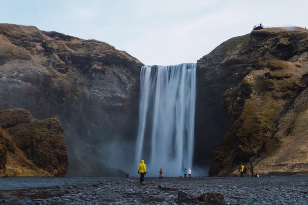 Cachoeira skogafoss cercada por pessoas e pedras sob um céu nublado na islândia